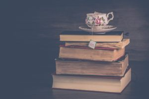 A floral-patterned teacup on a saucer sits on a stack of thick books with yellowed pages.