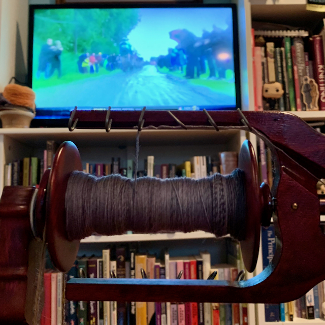 Gray yarn on spinning wheel bobbin in foreground, television screen showing a bike race in the background
